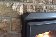 Stove inserted into stone fireplace.